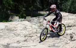 Idrottsmannen i sportswear på en mountainbike rider på stenarna I Royaltyfria Foton