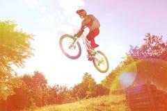 Idrottsmannen på en mountainbike flyger i ett hopp från en språngbräda Arkivfoton