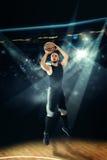 Idrottsmannen som spelar basket, och shootnig tre pekar skottet Arkivbild