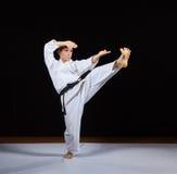 Idrottsmannen utbildar karateslag mot en svart bakgrund Royaltyfri Bild