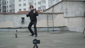 Idrottsmannen visar slaglängder på videokameran för blogg på ett tak 4K lager videofilmer