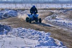 Idrottsmanracerbilmannen fullgör en snabb ritt på ATVEN på vägytterligheten Loppspåret är mycket ojämnt solig vinter för dag Arkivbilder