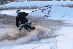 Idrottsmanracerbilmannen fullgör en snabb ritt på en motorcykel på vägytterligheten Loppspåret är mycket ojämnt Foto som racerbil Fotografering för Bildbyråer