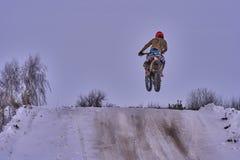 Idrottsmanracerbilmannen fullgör en snabb ritt på en motorcykel på vägytterligheten Loppspåret är mycket ojämnt Foto som racerbil Arkivfoton