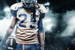 Idrottsmanspelare för amerikansk fotboll på stadion med ljus på bakgrund Arkivbild