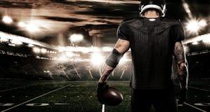 Idrottsmanspelare för amerikansk fotboll på stadion Sportbaner och tapet med copyspace royaltyfria foton