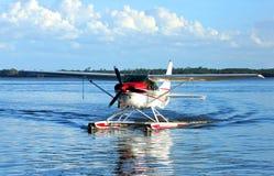 Idrovolante del singolo motore sulle acque blu e sui cieli blu nei precedenti fotografie stock libere da diritti