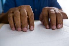 idsection des älteren Mannes Blindenschrift-Buch im Pflegeheim lesend Lizenzfreies Stockfoto