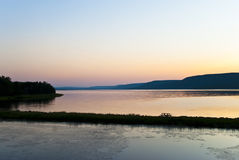 Idylic Picnic. Picnic Table on Thin Finger of Land with Calm Lake and Distant Hills during Sunset Stock Photography