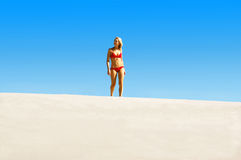 Idyliic beach walk. A fit , healthy young woman walking on the beautiful white sands of a tropical island. The perfect blue sky provides a magnificent backdrop stock photo