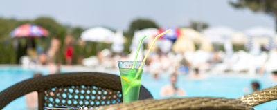 Idyll relaxation with cold drink next to the swimming pool Royalty Free Stock Images