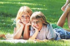 Idylle de famille Mère et fils sur la pelouse verte Photos libres de droits