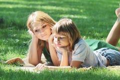 Idylle de famille Mère et fils sur la pelouse verte Image libre de droits
