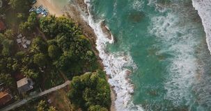 Idyllic aerial view of exotic resort beach with little boat, houses and hotels, foaming white waves crashing at shore. Idyllic aerial view of exotic resort stock video