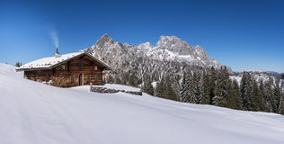 Idyllic alpine hut in the Alps. The mountains in the Austrian province of Salzburg show up in winter Royalty Free Stock Photography