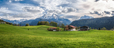 Idyllic alpine landscape with green meadows, farmhouses and snowcapped mountain tops Royalty Free Stock Photo