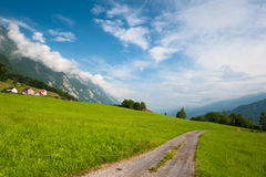Idyllic Alpine meadow with road. Switzerland. Idyllic Alpine meadow with road in green grass under blue cloudy sky in Switzerland Stock Image