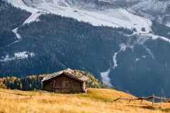 Wooden cottage in dolomities alps Italy. Idyllic alpine mountain scenery with traditional old mountain wooden cottage in Seceda peak, Dolomiti. South Tyrol Royalty Free Stock Photos