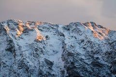 Idyllic alpine snowy mountain chain peak view in orange sunset sky, julian alps, Slovenia Royalty Free Stock Images