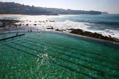 Idyllic and amazing seaside public swimming pool with landscape of jagged shoreline with rocks, white rushing crashing sea waves stock photo