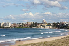 Idyllic beach bay with town Stock Images