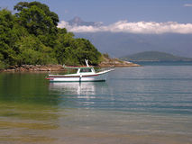 Idyllic beach and boat. Scenic view of boat in picturesque bay with Tangua beach in foreground, Angra dos Reis, Rio de Janeiro, Brazil Stock Photo