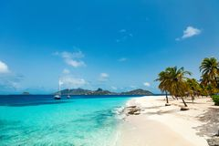 Idyllic beach at Caribbean. Idyllic tropical beach with white sand, palm trees and turquoise Caribbean sea water on exotic island in St Vincent and the royalty free stock photo