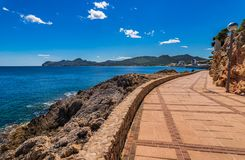 Promenade at coast of Cala Ratjada on Mallorca island. Idyllic boardwalk at the seaside in Cala Rajada, Mallorca, Spain Balearic islands Stock Photo