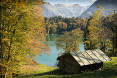 Idyllic cabin in fall at a turquoise lake Royalty Free Stock Photo