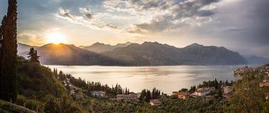Idyllic coastline in Italy: Blue water and a cute village at lago di garda, Malcesine, sunset. Summer holidays in the Dolomites: Idyllic coastline at lago di stock photo