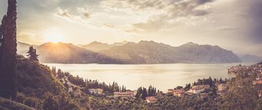 Idyllic coastline in Italy: Blue water and a cute village at lago di garda, Malcesine, sunset. Summer holidays in the Dolomites: Idyllic coastline at lago di royalty free stock image