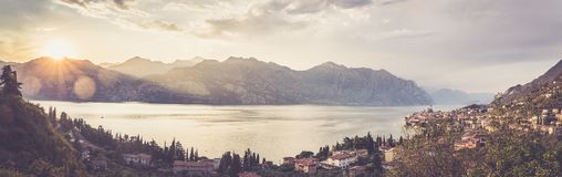 Idyllic coastline in Italy: Blue water and a cute village at lago di garda, Malcesine, sunset. Summer holidays in the Dolomites: Idyllic coastline at lago di royalty free stock images