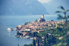 Idyllic coastline scenery in Italy: Blue water and a cute village at lago di garda, Malcesine. Cute idyllic Italian village and lake captured from above royalty free stock images