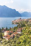 Idyllic coastline scenery in Italy: Blue water and a cute village at lago di garda, Malcesine. Cute idyllic Italian village and lake captured from above royalty free stock image
