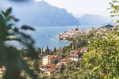 Idyllic coastline scenery in Italy: Blue water and a cute village at lago di garda, Malcesine. Cute idyllic Italian village and lake captured from above stock photo