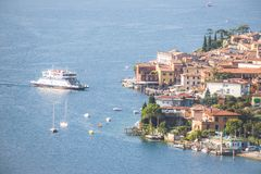 Idyllic coastline scenery in Italy: Blue water and a cute village at lago di garda, Malcesine. Cute idyllic Italian village and lake captured from above stock photos