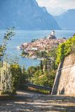 Idyllic coastline scenery in Italy: Blue water and a cute village at lago di garda, Malcesine. Cute idyllic Italian village, moutain road and lake captured from stock images