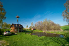 Idyllic countryside getaway. In Poland with pond, stork on the pole and car parked Stock Photo