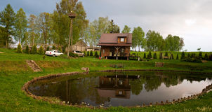 Idyllic countryside getaway. In Poland with pond, stork on the pole and car parked Stock Photography