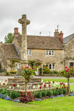 Stone cross in garden, Castle Combe Village, Wiltshire, England Stock Images