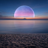 Idyllic fantasy scenery with ocean and planet on horizon Royalty Free Stock Photography