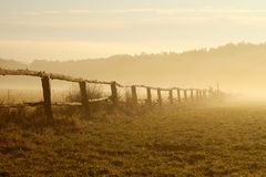 Idyllic fence on a misty field at sunrise. Idyllic fence on the pasture of horses with morning mist floating above the ground. Photo taken at sunrise. Forest in Royalty Free Stock Photo