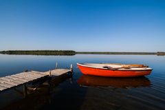 Summer Lake. A beautiful idyllic view of a glassy lake in northern Sweden. The sky is perfectly blue and you see a rowing boat with fishing gear docked by a Royalty Free Stock Photos