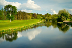 Idyllic golf course at the river. Idyllic golf course with reflection in the river Stock Photo