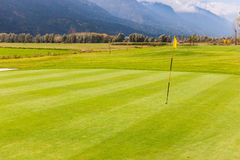 Idyllic golf course view. A golf hole with a flag pole in a beautiful golf course Stock Photo