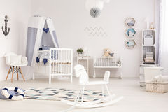 Idyllic infant room ready to welcome its first occupant. Unique infant room with marine decorative elements and a white rocking horse in the foreground Royalty Free Stock Images
