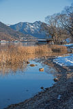 Idyllic lake shore with boathouse, at the end of winter, tegerns Royalty Free Stock Photo