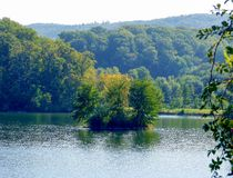Idyllic lake with tree island and forest in the background. Idyllic south german landscape with tree island in lake and forest, small island with trees in the royalty free stock image