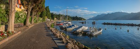 Idyllic lakeside promenade malcesine at sunny afternoon. Idyllic sunny lakeside promenade malcesine with moored colorful sailboats and mediterranean shore royalty free stock photos