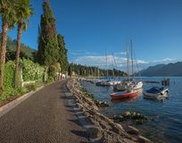 Idyllic lakeside promenade malcesine. Idyllic sunny lakeside promenade malcesine with moored sailboats bob up and down in the water stock photography